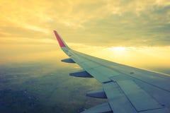 Ala de un vuelo del aeroplano sobre las nubes en la puesta del sol (Filtro Fotos de archivo