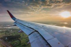 Ala de un vuelo del aeroplano sobre las nubes en la puesta del sol (Filtro Fotografía de archivo