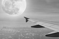 Ala del aeroplano con el fondo del cielo nocturno del supermoon Imagenes de archivo