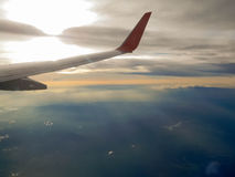Ala del aeroplano de la ventana con luz del sol hermosa y la nube Fotos de archivo