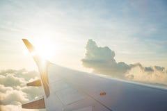 Ala del aeroplano en el cielo de la nube de la ventana por mañana Imagenes de archivo