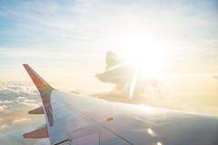 Ala del aeroplano en el cielo de la nube de la ventana por mañana Imagen de archivo