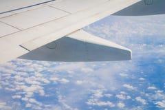 Ala del aeroplano en el cielo y sobre el mar con las nubes Imagen de archivo libre de regalías