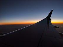 Ala del aeroplano en la oscuridad, horizonte colorido Imágenes de archivo libres de regalías