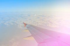 Ala del aeroplano en vuelo de la ventana sobre las nubes y el cielo Foto de archivo libre de regalías