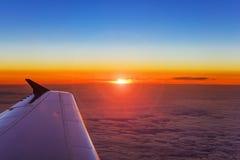 Ala del aeroplano en vuelo sobre las nubes en el fondo de la puesta del sol Fotos de archivo