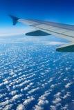 Ala del aeroplano fuera de la ventana, del cielo azul y de las nubes Imagenes de archivo