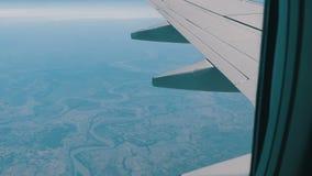 Ala del avión a través de la porta El avión vuela sobre las nubes hermosas del aire metrajes
