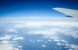 Ala del avión en fondo del cielo azul y nevoso Imagenes de archivo