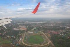 Ala del volo dell'aeroplano sopra la città Fotografia Stock