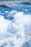 Ala del vuelo del aeroplano sobre las nubes y el cielo azul Fotos de archivo libres de regalías