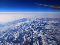 Ala di un aereo di linea sopra le montagne immagini stock
