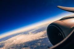 Ala e turbina degli aerei attraverso la finestra contro il cielo con le nuvole Fotografie Stock