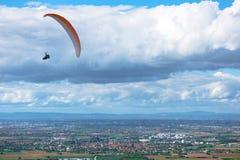 Ala flexible que vuela sobre campos y ciudades foto de archivo