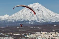 Ala flexible que vuela sobre ciudad en fondo del volcán activo Imagen de archivo libre de regalías