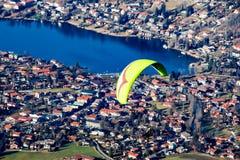 Ala flexible que vuela sobre una ciudad y un lago Imagen de archivo libre de regalías