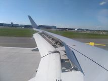 Ala izquierda del aeroplano en la pista foto de archivo