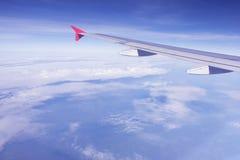 Ala plana que vuela sobre la nube del blanco del cielo azul Imagen de archivo libre de regalías