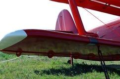 ala rossa del biplano sulla terra immagini stock