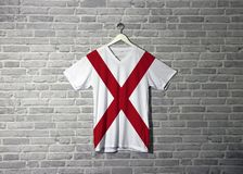 Alabama flag on shirt and hanging on the wall with brick pattern wallpaper. The states of America stock photos