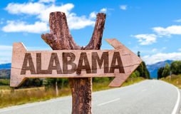 Alabama wooden sign with road background Stock Photos