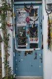 Alacati有一个美妙的村庄门,装饰用围巾,鞋带,经典蓝色被绘的门 库存图片