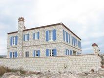 Alacati有蓝色快门的石头房子 免版税库存图片