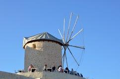 Alacati, Izmir, die Türkei: Am 13. Oktober 2013: Ansicht des alten wildmill in Alacati Leute genießen Zeit in einem Café nahe Win Lizenzfreie Stockfotos