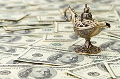 Aladdin lamp on dollar background Stock Photos