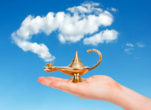 Aladdin lamp in hand. Aladdin lamp in human hand against cloudy sky stock image