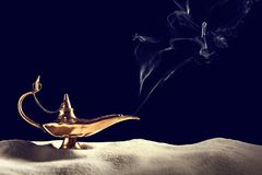 Aladdin magic lamp on sand. Against black background royalty free stock photos