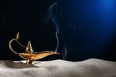Aladdin magic lamp on sand. Against dark background royalty free stock photography