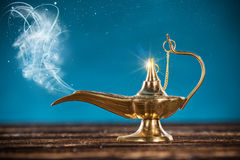 Aladdin magic lamp with smoke. Aladdin magic lamp on wooden table with smoke stock images