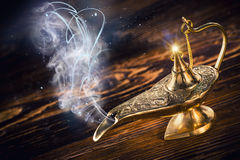 Aladdin magic lamp with smoke. Aladdin magic lamp on wooden table with smoke royalty free stock photos