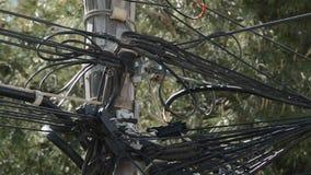 Alambre de los cordones de la electricidad y de la telefonía instalado gravemente en un polo de madera