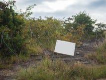 Alambre de púas con la cartelera en blanco en el campo de batalla Imagenes de archivo