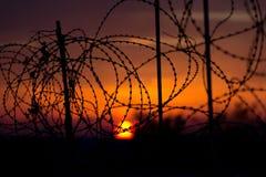 Alambre de púas contra el cielo de la puesta del sol. imagenes de archivo
