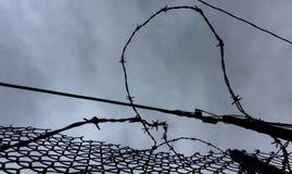 Alambre de púas debajo de un cielo cubierto Imagen de archivo