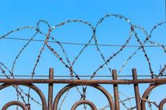 Alambre de púas en una cerca contra el cielo azul Foto de archivo