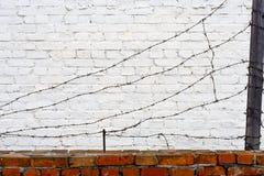 Alambre de púas en una pared de ladrillo Foto de archivo