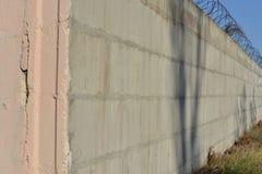 Alambre de púas estirado a lo largo de las paredes pintadas ladrillo fotografía de archivo libre de regalías