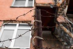 Alambre de púas oxidado y un edificio con las ventanas y las escaleras Foto de archivo