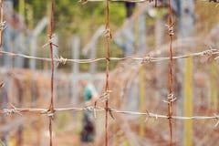 Alambre de púas, una cerca en la prisión y la silueta de un oficial de prisiones en el fondo Imagenes de archivo