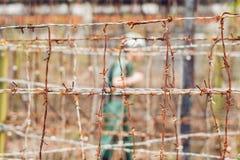 Alambre de púas, una cerca en la prisión y la silueta de un oficial de prisiones en el fondo Imagen de archivo
