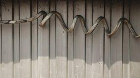 Alambre eléctrico espiral sucio grueso en la pared de acero acanalada foto de archivo libre de regalías
