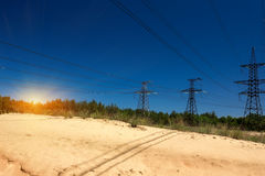 Alambres de alto voltaje en un fondo de la salida del sol Imagen de archivo