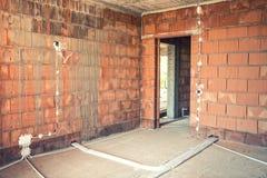 Alambres e instalación del zócalo y tubos de electricidad en emplazamiento de la obra de la casa Foto de archivo libre de regalías