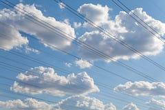 Alambres eléctricos contra el cielo azul y las nubes hermosas Foto de archivo libre de regalías