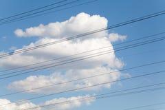 Alambres eléctricos contra el cielo azul y las nubes hermosas Imagen de archivo libre de regalías