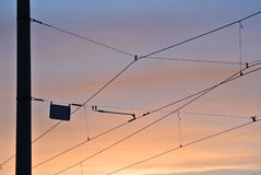 Alambres eléctricos de la tranvía, cielo de la puesta del sol fotos de archivo